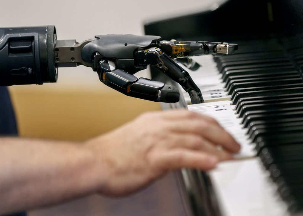 view from the side of a mechanical hand next to a person's hand, both playing the piano