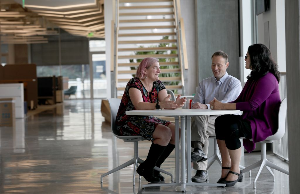 trio of researchers sitting in a foyer at a table, talking