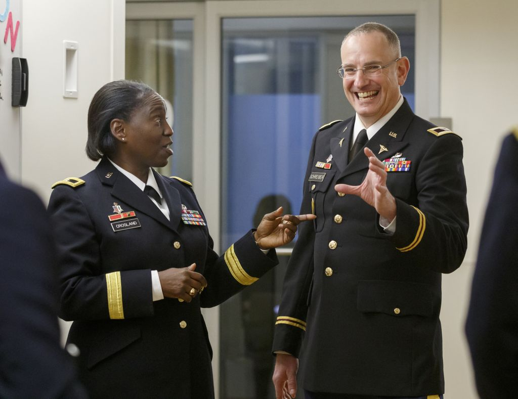 two Army personnel in uniform talk and smile with one another