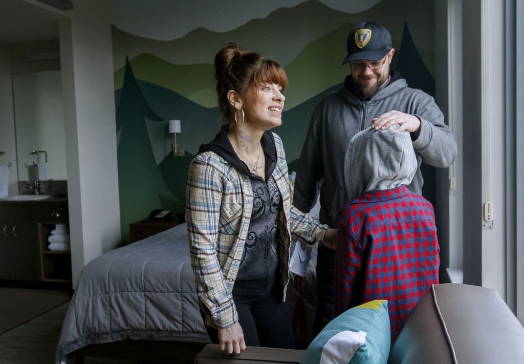 parents and child moving into a room at the ronald mcdonald house, looking out the window of their room