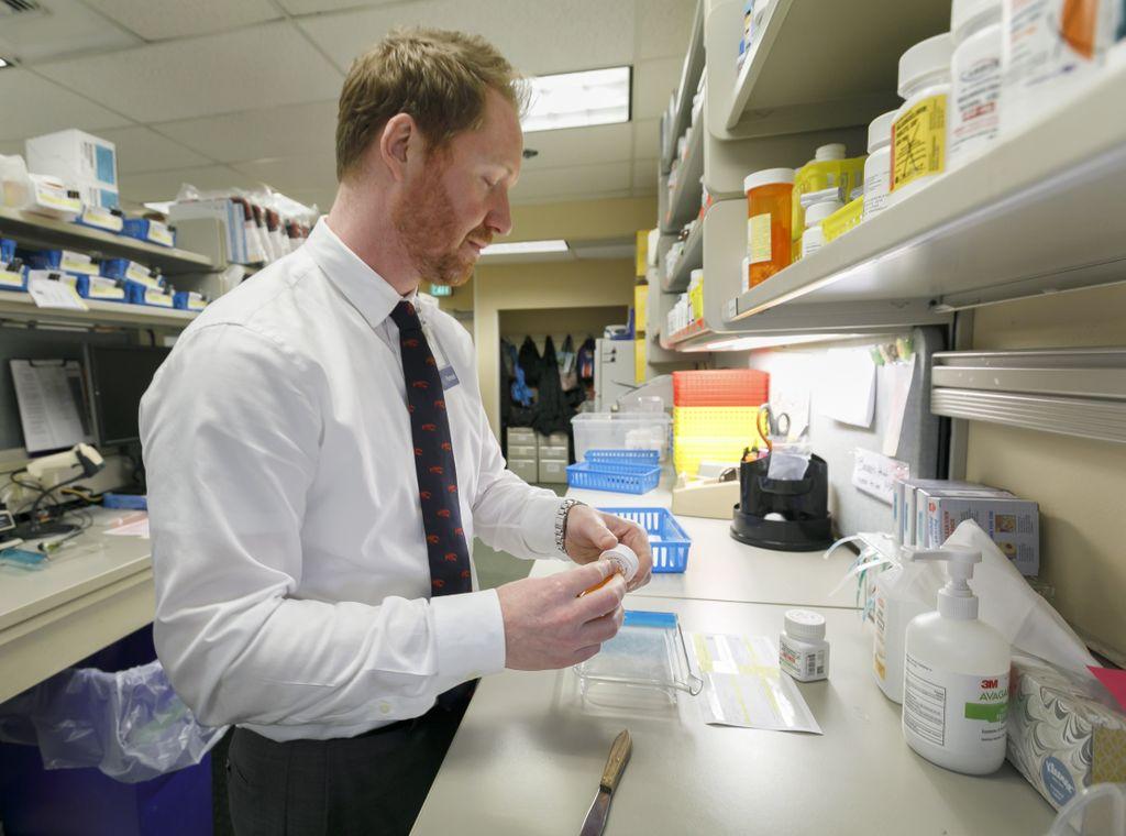 pharmacist bottling up medication at pharmacy