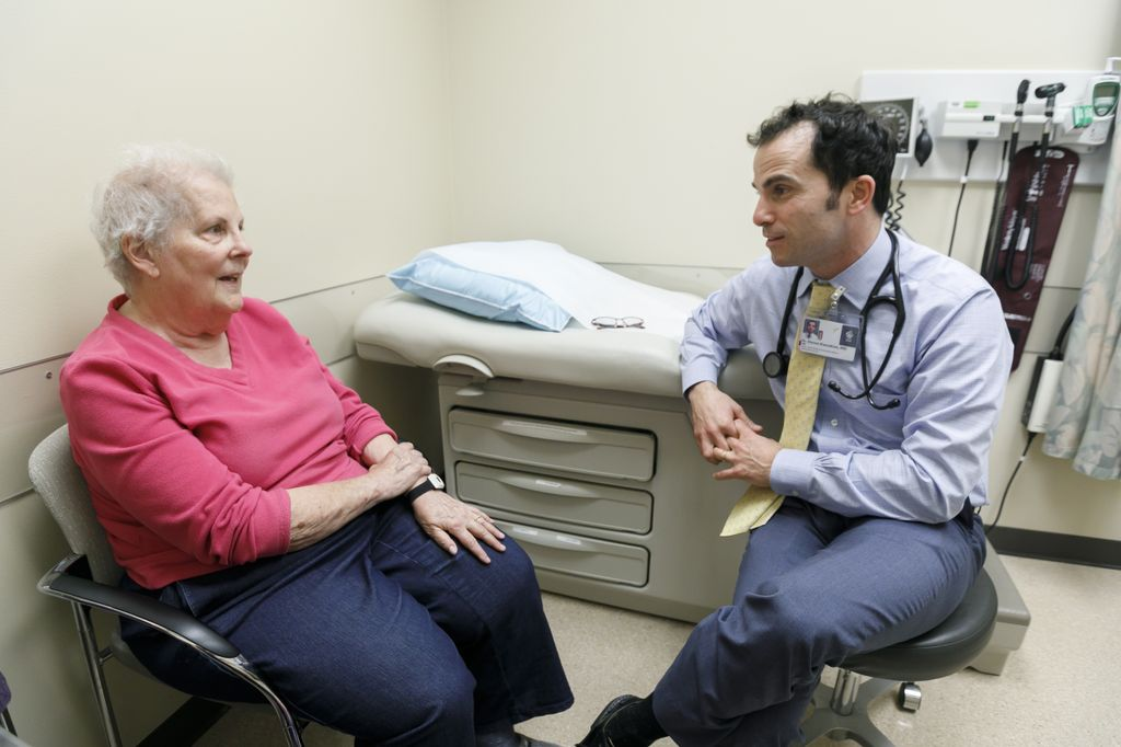 patient wearing a pink shirt on left, seated, meeting with doctor on right, seated, in a doctors office