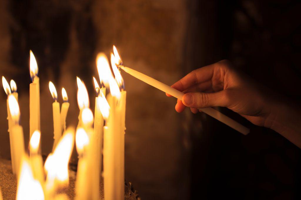 closeup of hand lighting candles