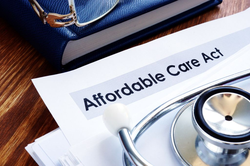 paper that says affordable care act with a stethoscope lying on top and a pair of glasses
