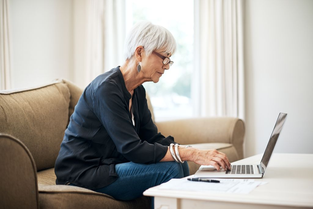senior woman sitting on a couch, working on a laptop computer