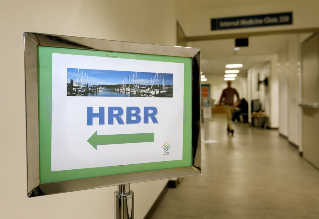 sign that says hrbc with an arrow pointing to the left, in a hallway of a medical office