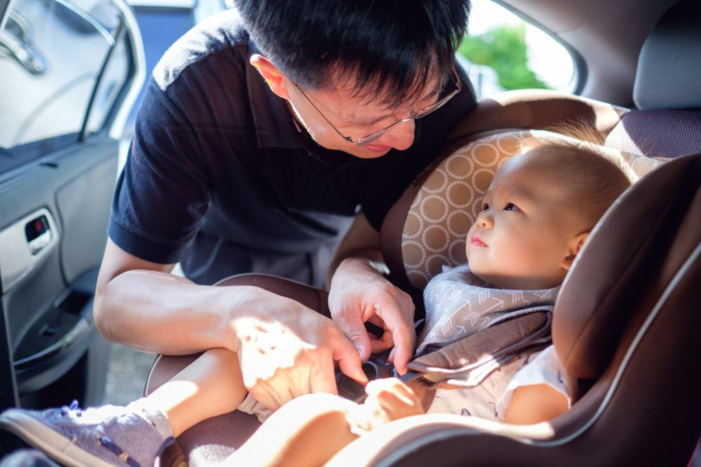 asian dad buckling an infant into a car seat