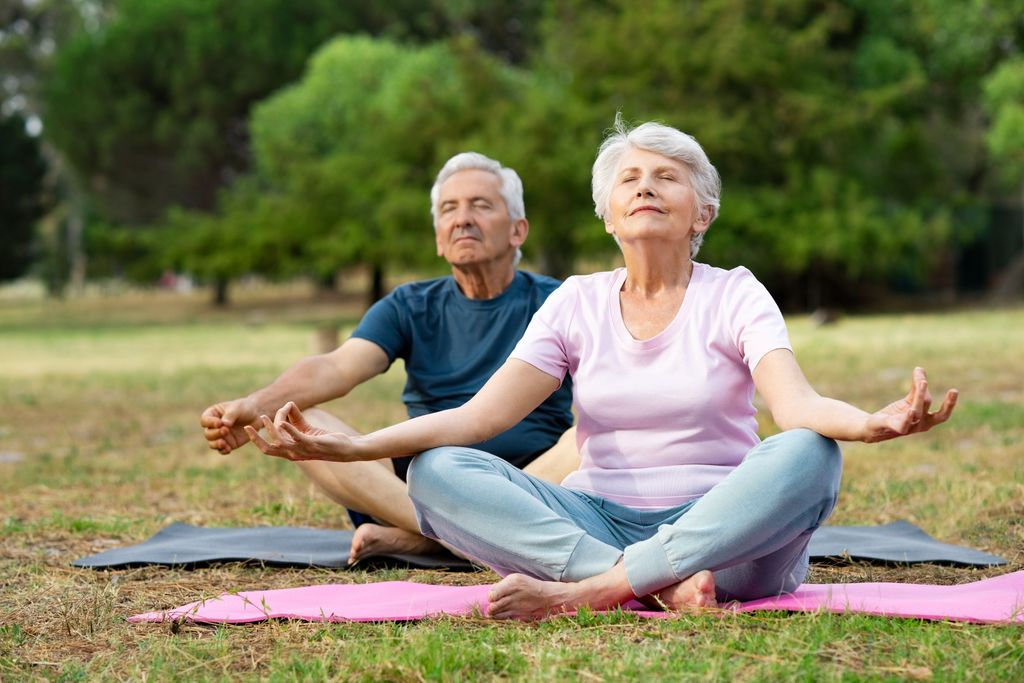 senior man and woman, sitting cross legged in a field, in a mediation pose
