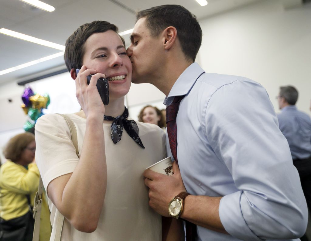 woman on the phone with a man kissing her cheek