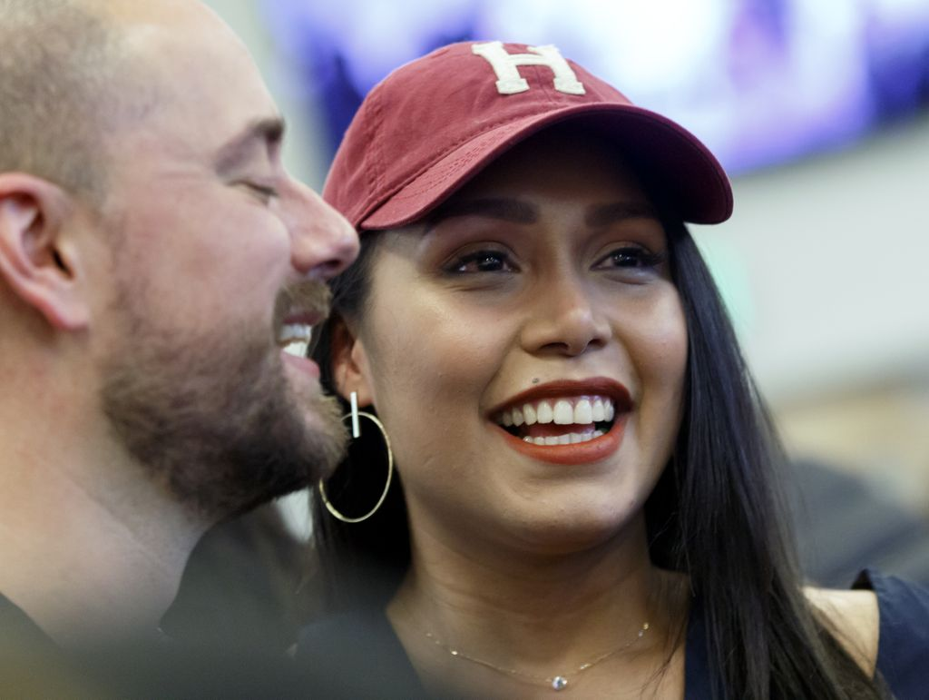 woman wearing red baseball hat with a Harvard H on the front