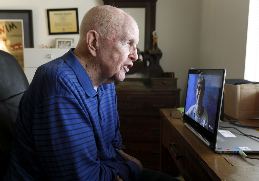 bald, older man chatting with someone via video