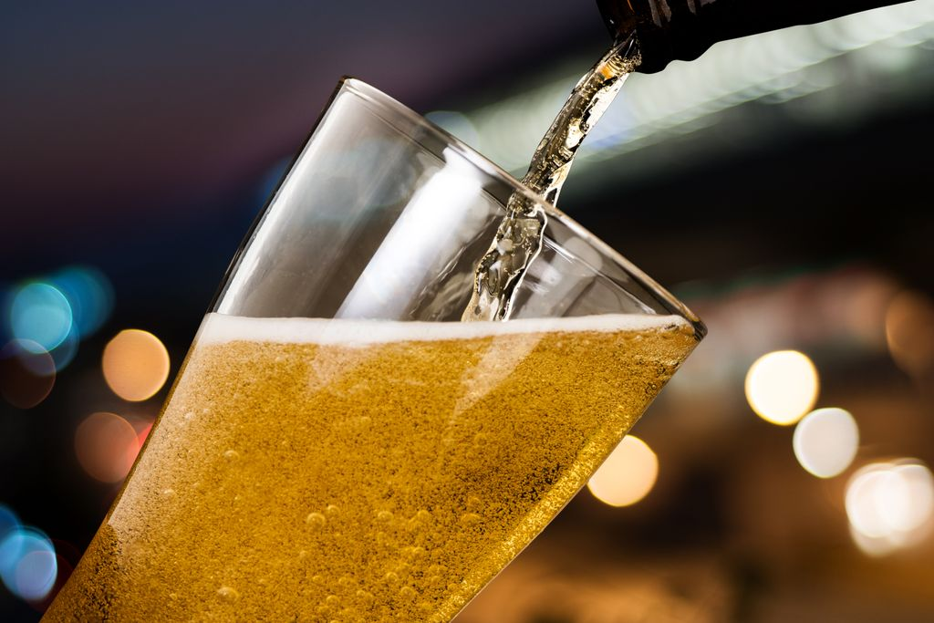 bottle pouring beer into a glass