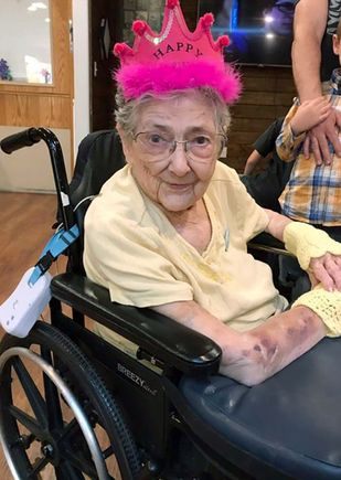 geriatric woman wearing a pink birthday hat, sitting in a wheelchair