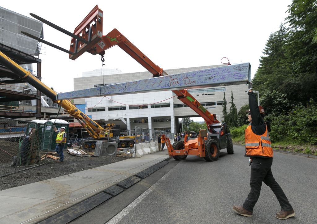 construction worker reaching up to stabilize large iron beam being moved by a crane