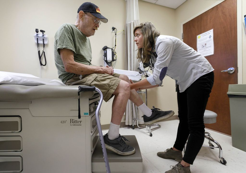 female doctor looking at the knee of an elderly man