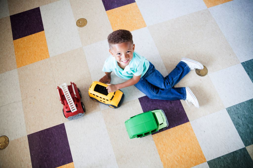overhead view of a child playing on the floor with some trucks