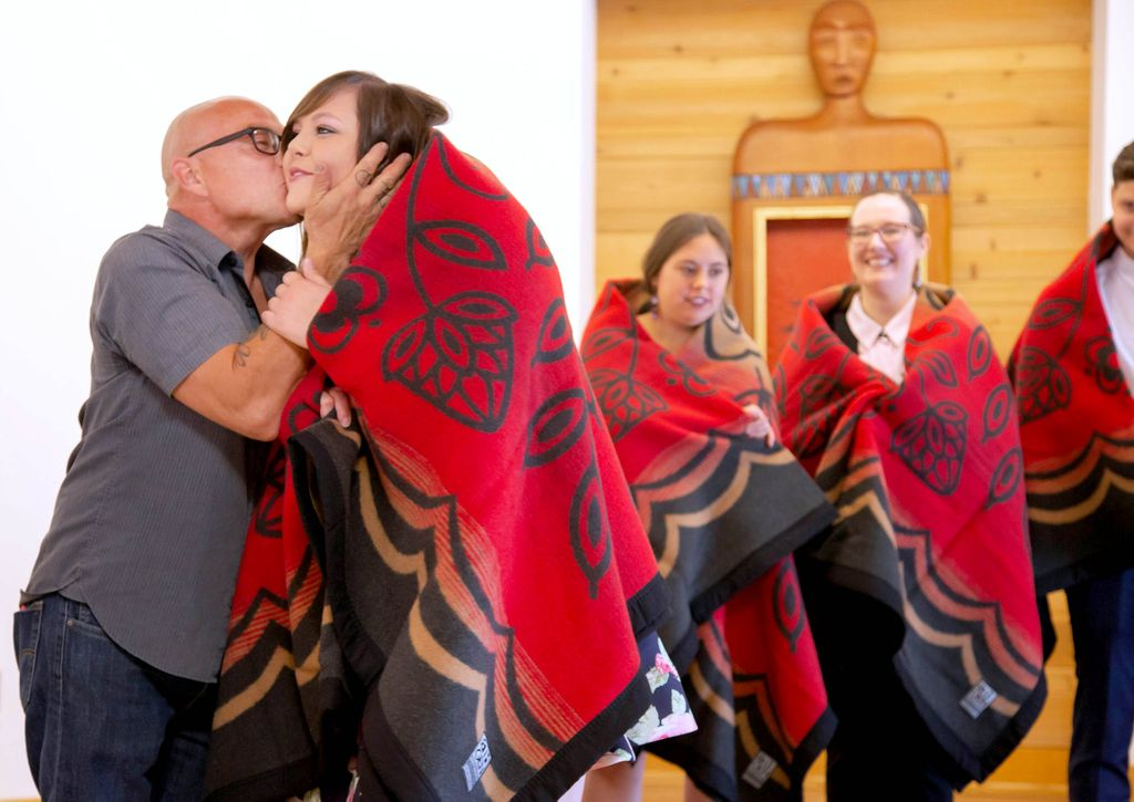 A young woman wears a red patterned wool blanket over her shoulders as a bald man kisses her on the cheek and two other young women also wearing red wool blankets watch behind them.