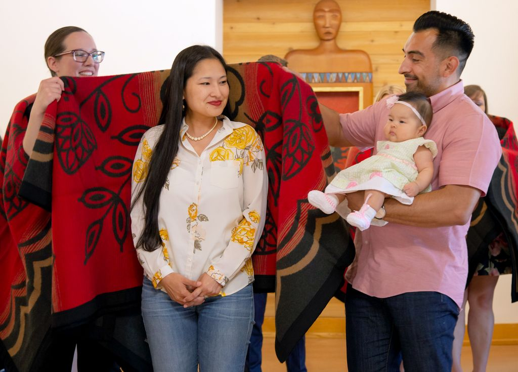 jessica's shoulders are draped with a blanket, as she looks towards her husband and baby