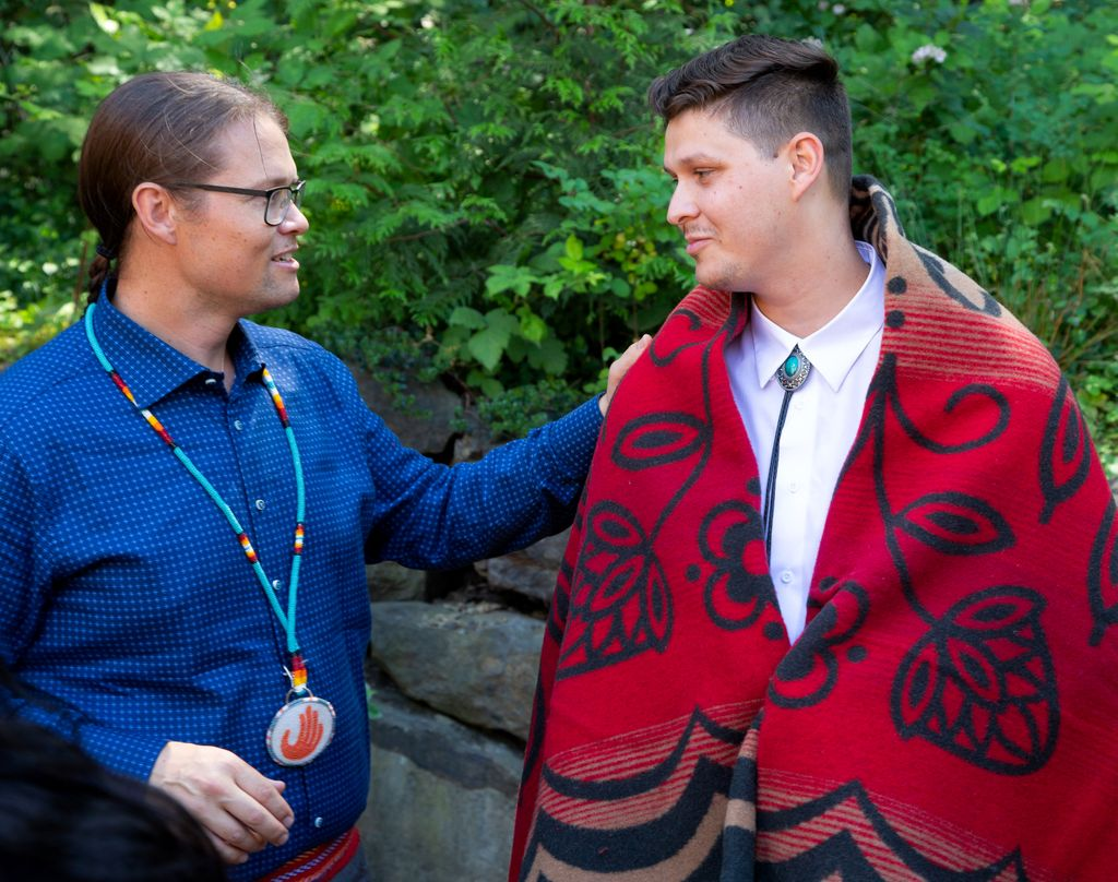 erik brodt talks with a young native american student, who has a red blanket draped over his shoulders