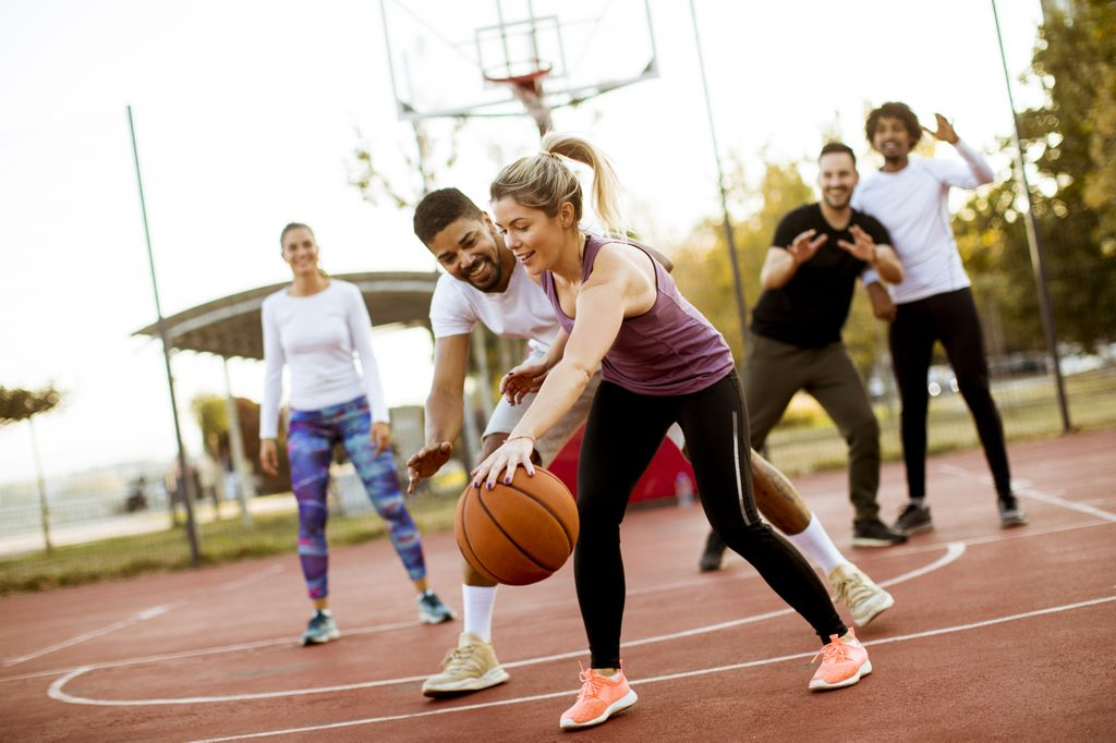diverse group of men and women playing in a pick-up basketball game