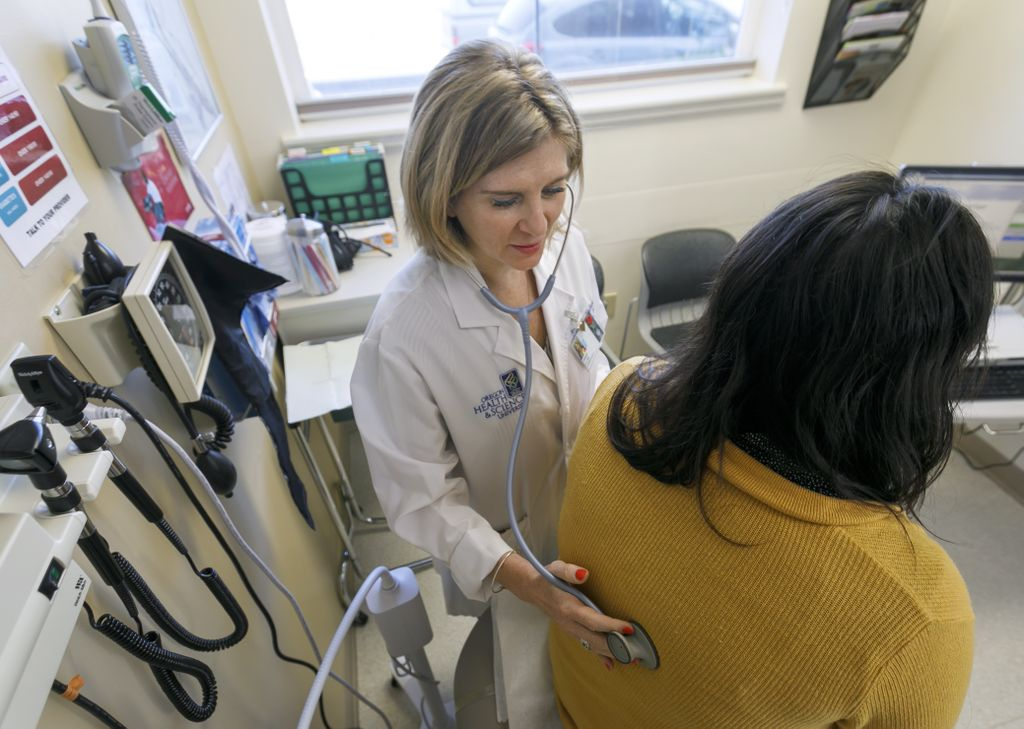 image of medical professional listening to a patient's lungs with a stethoscope in a doctor's office