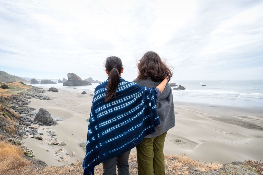two women wrapped in blankets, standing with arms around one another on a beach, seen from behind