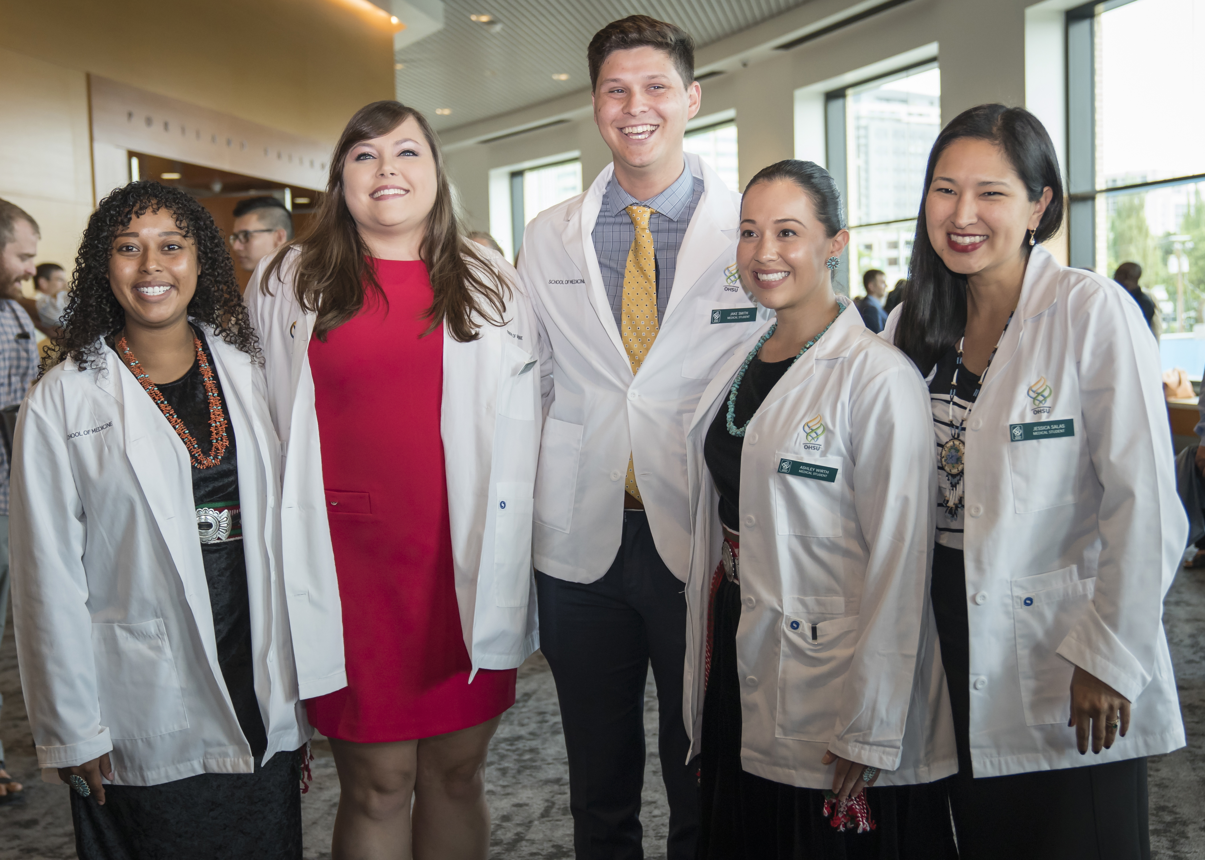 five native american students, wearing white coats and smiling at camera