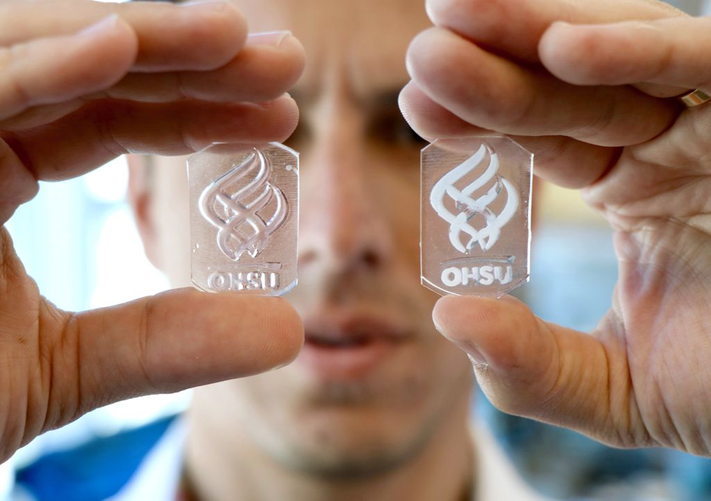 close up photo of bertassoni holding two slices of engineered material with the ohsu logo, one in each hand, in front of his face, with face out of focus in background