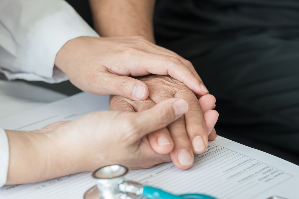 close up of a a pair of hands, holding another hand, on top of a clipboard, with a stethoscope