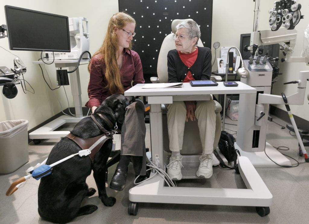 kathryn sits on left, helping beverly on right, teaching her to use a reader to read a newspaper, as kathryn's seeing eye dog nabisco sits at kathryn's fit on the left