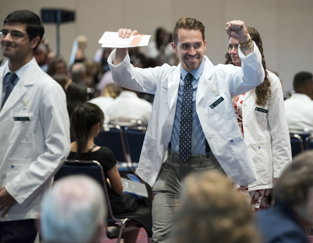 student wearing a white coat, walking between the aisles with his arms in fists, raised above his head