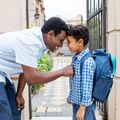 Smiling father leaving son with backpack to school