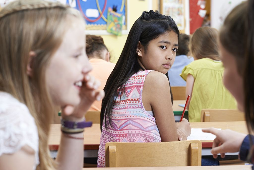 girl in center of image, seated at her desk in a classroom looking back over her shoulder looking at two girls gossiping about her