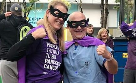 two people, woman and man, in masks and purple capes