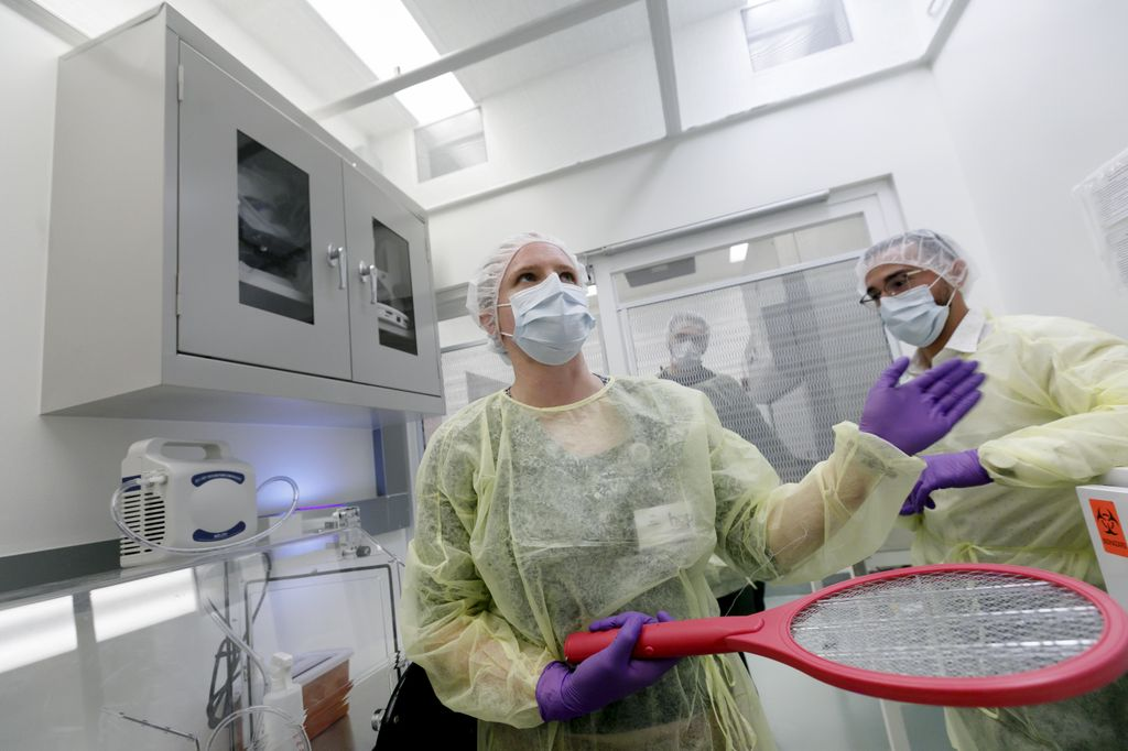 woman and man, fully clothed in protective clothing, in a small research room, holding an electrified tennis racket which is a bug zapper