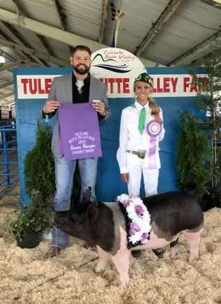 quiana, right, dressed in white and holding up a ribbon as she stands behind a large show pig at the fair
