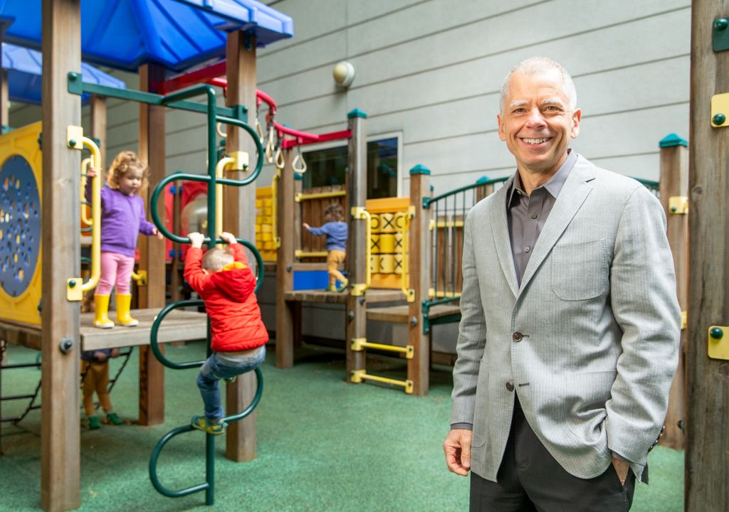 older gentleman with short gray hair wearing a gray suit with hands in pockets, smiling at camera, standing on playground with children playing on playground equipment behind him