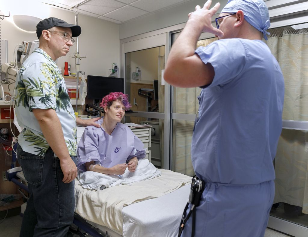 female patient sits on a bed as her husband on her left, wearing a ball cap, talks to the anesthesiologist, wearing scrubs, on her right