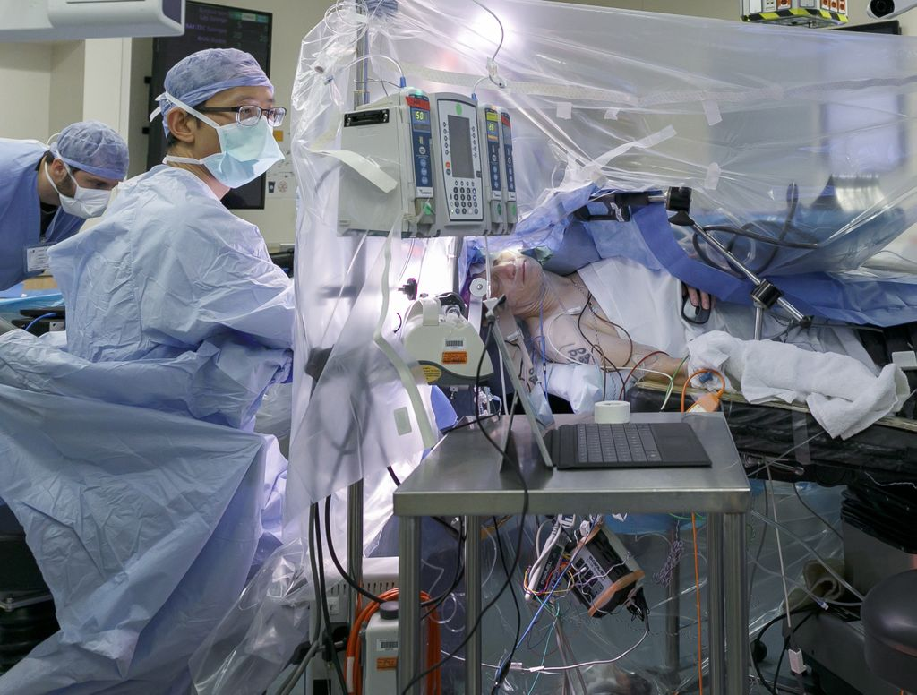 doctor in full scrubs in operating room, talking to patient lying on operating table during a surgical procedure