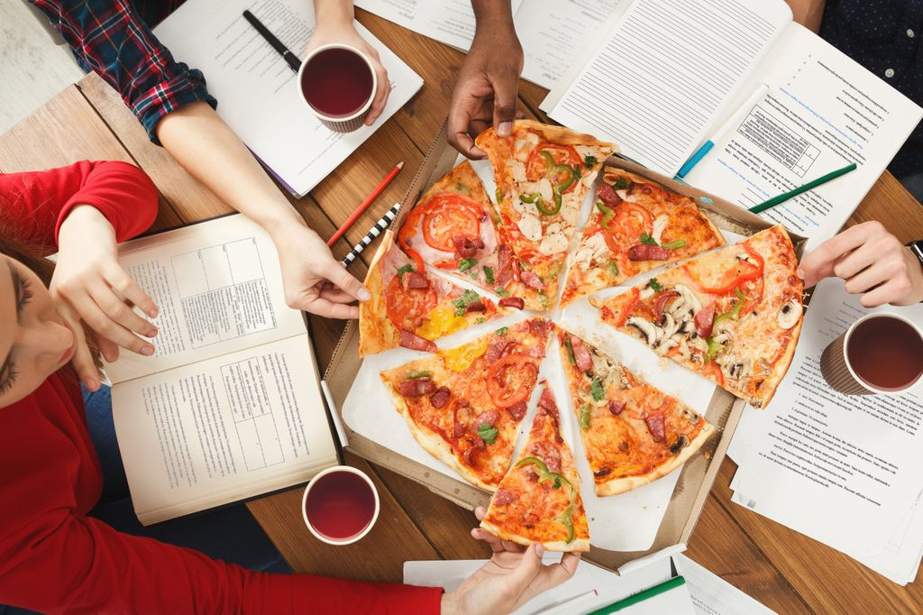 overhead view people sitting around a pizza, with books open, reading, and hands grabbing slices of pizza
