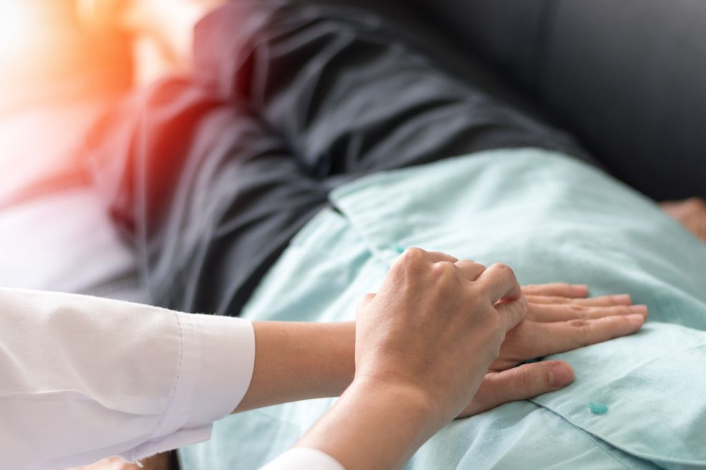 Patient laying on table with doctor's hands on stomach checking for disease