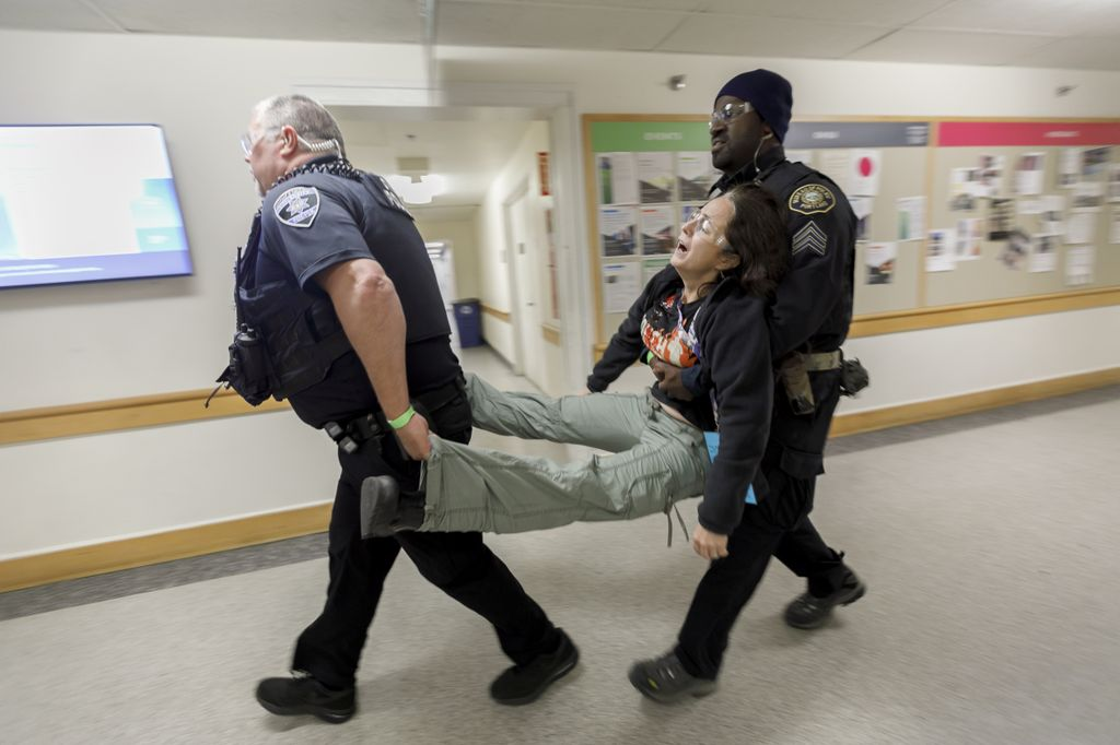 two police officers carry a woman between them