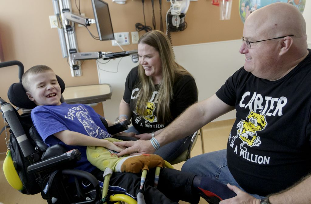 Carter, in his wheelchair, smiling with his parents.