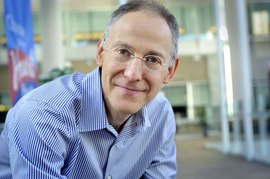 man in a blue shirt wearing glasses, pleasant smile, leaning over and looking at camera