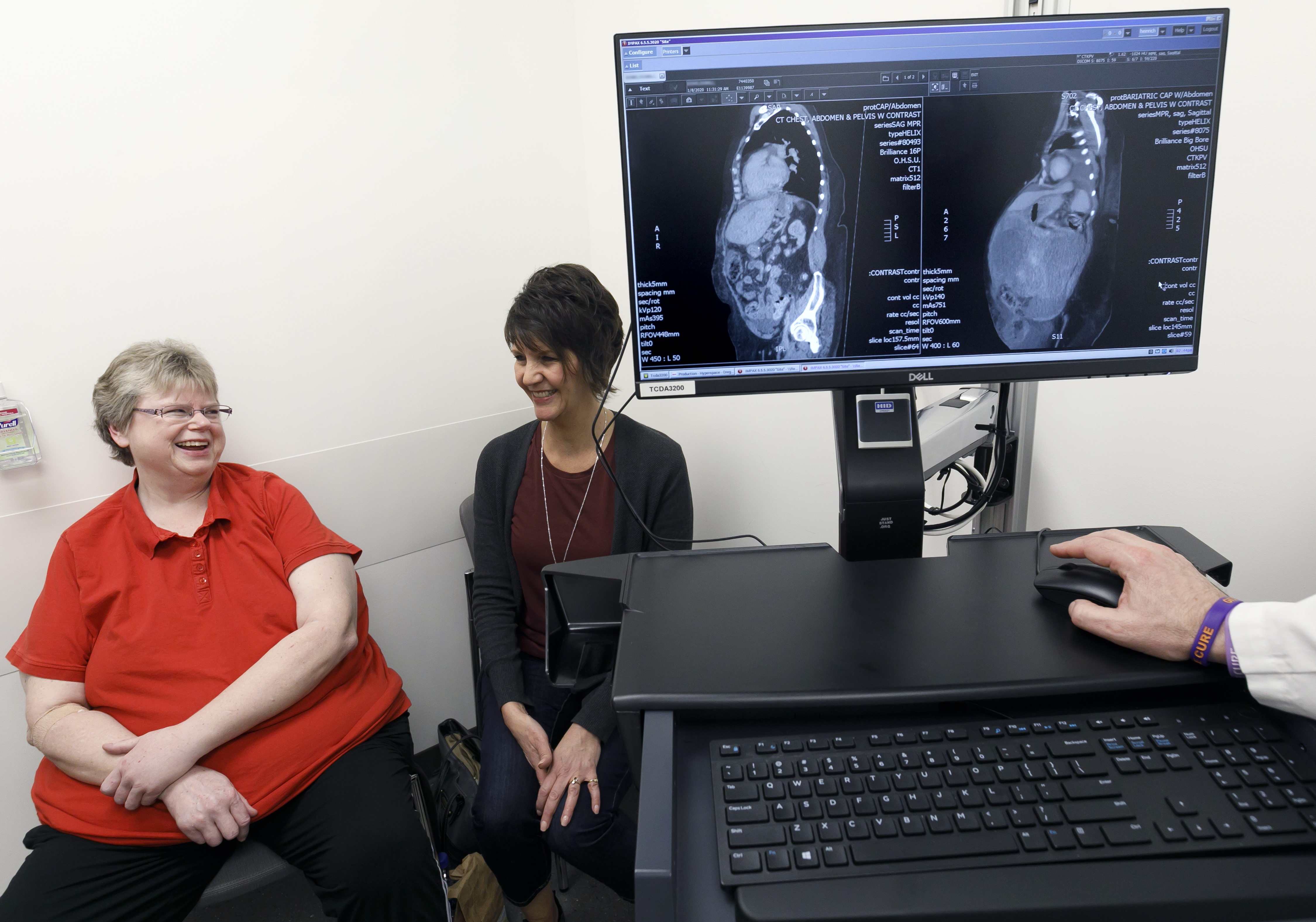 two women, seated and talking with another, with a computer monitor on the right side of the picture showing two xray scans, before and after, of the patient