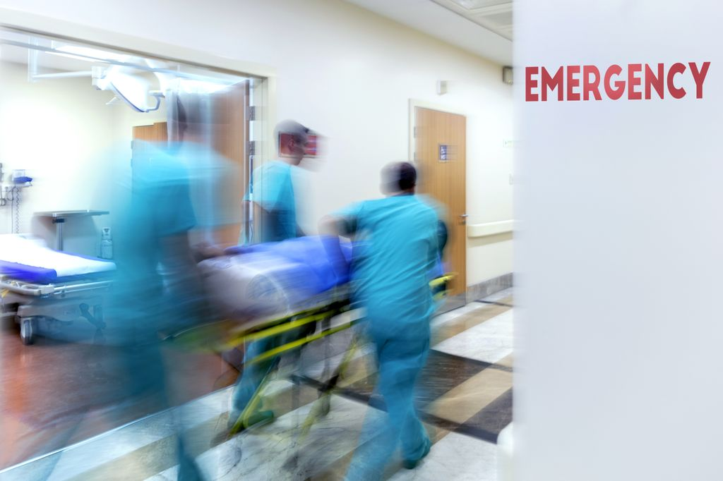 medical team wheeling patient down hall past a sign that says emergency
