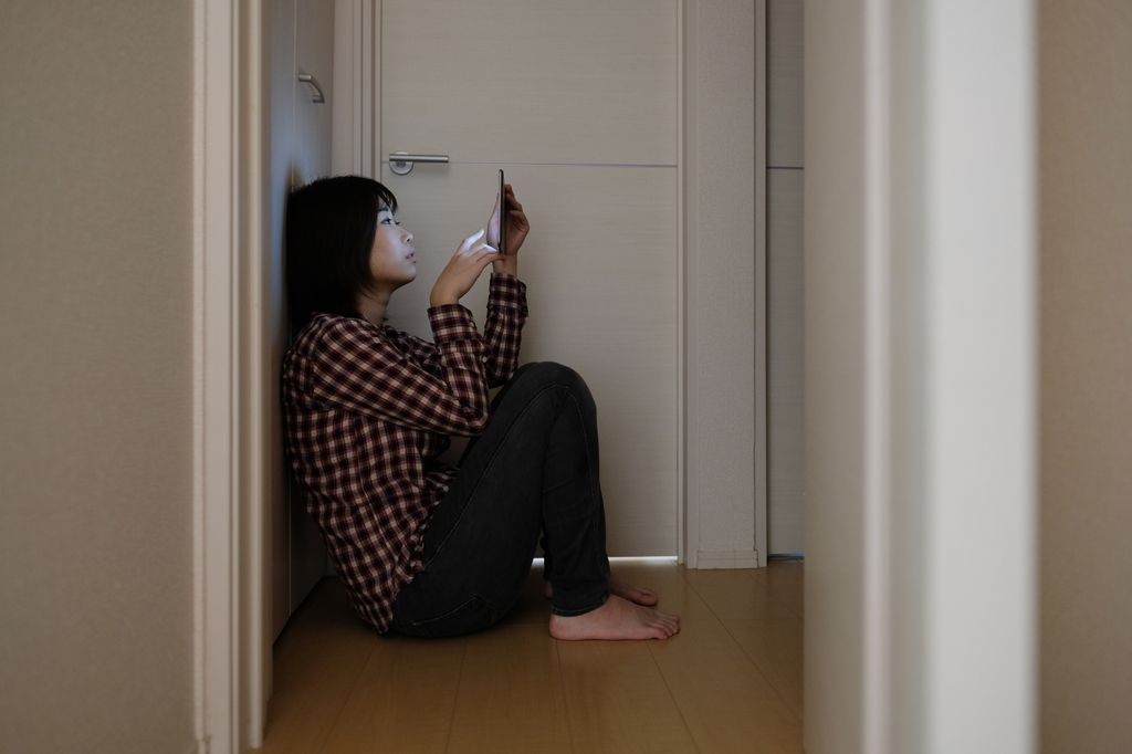 an asian woman sitting in a hallway alone, on the floor, leaning against a door as she looks at a mobile phone