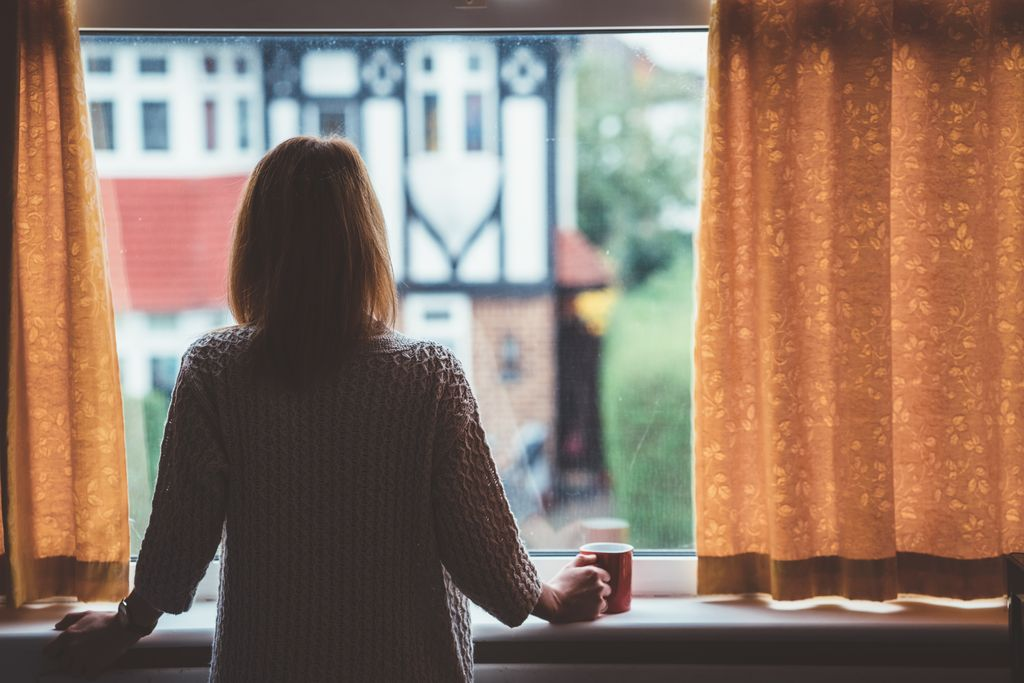 A woman looking out a window, standing alone.