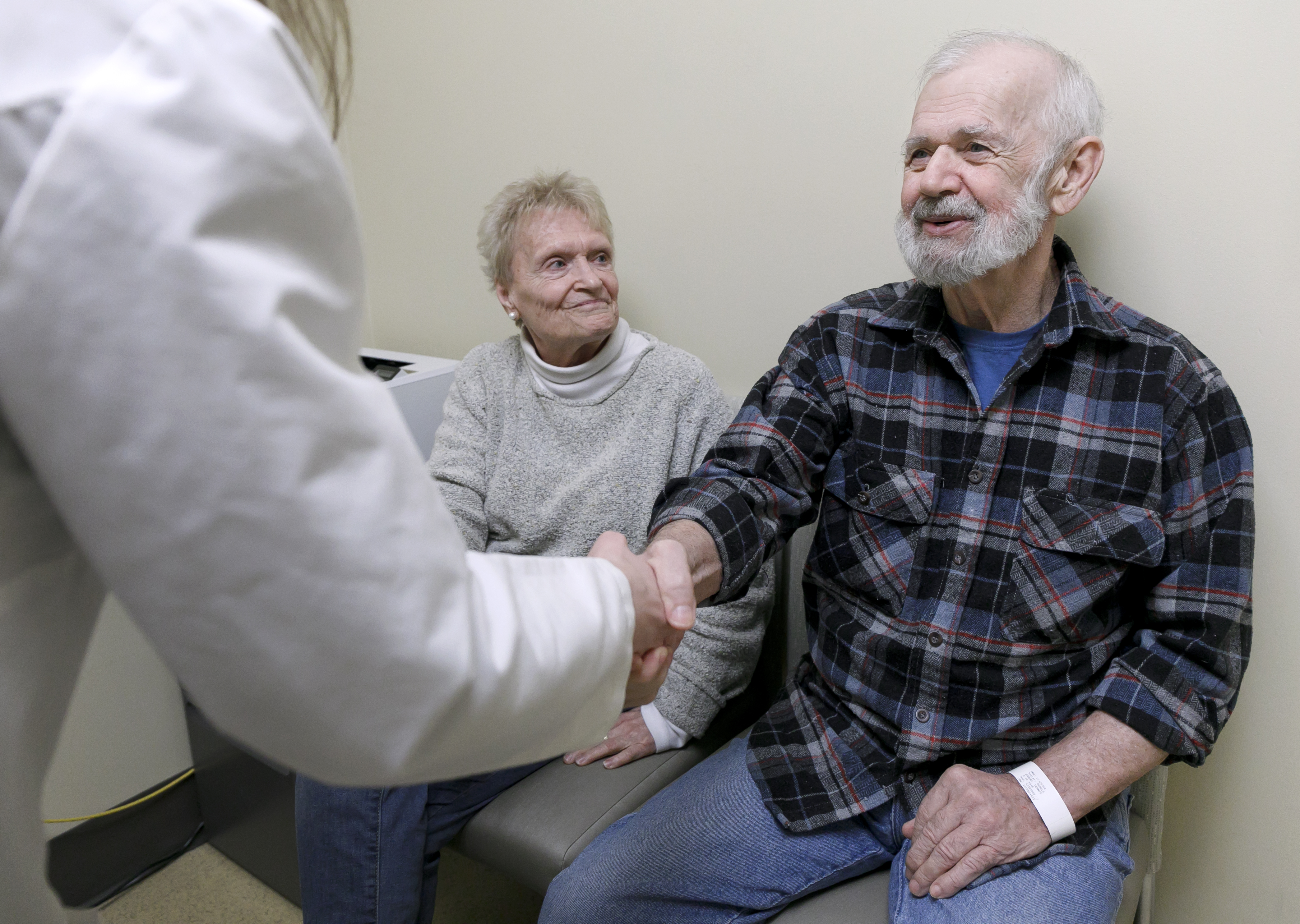 woman and man seated in doctor's office, woman looking at her husband as he shakes the hand of a doctor