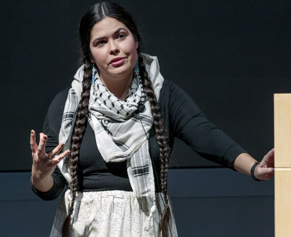 native american woman, with two long braids and wearing traditional clothing, lecturing on stage